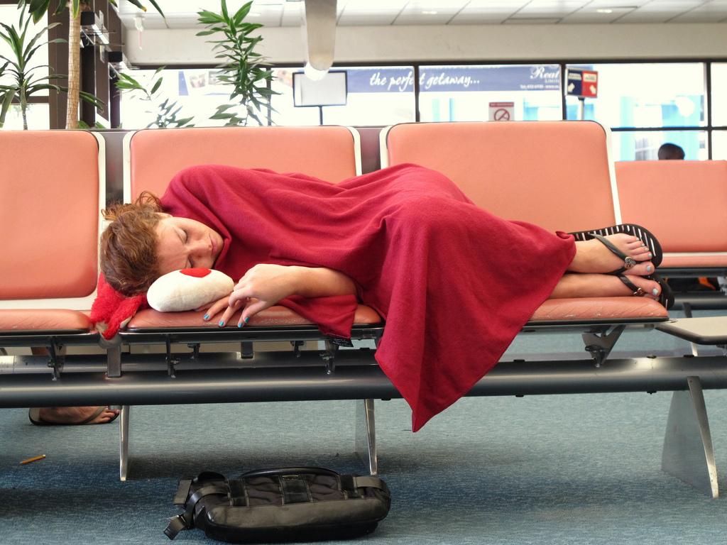 ragazza dormendo sulla sedia di un aeroporto